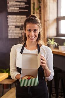 Kellnerin, die kästen mit einem kuchen nach innen hält