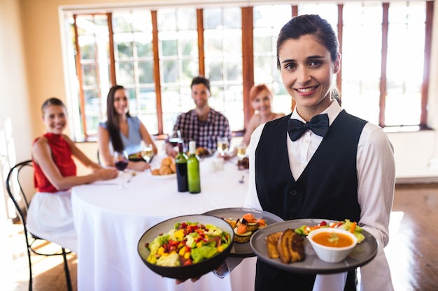Kellnerin, die lebensmittel auf platte im restaurant hält