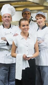 Kellnerin, die vor mannschaft von köchen steht