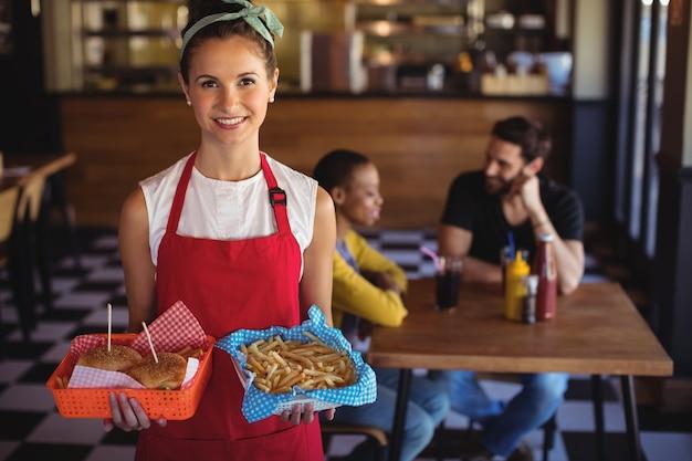 Kellnerin hält burger und pommes im tablett