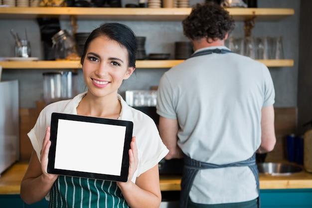 Kellnerin hält digitales tablett, während kellner im hintergrund arbeitet