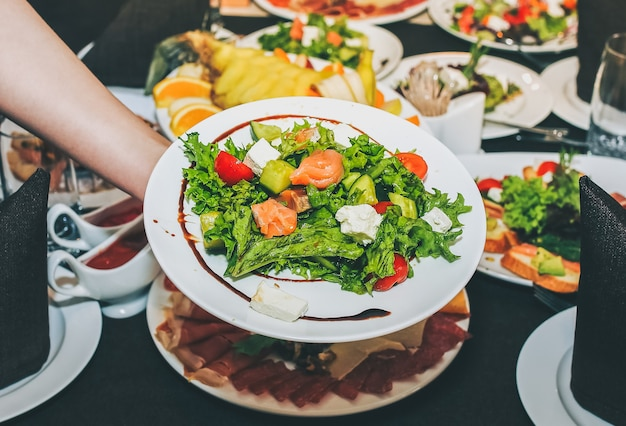 Kellnerin hält frischen salat in der hand. frau deckt den tisch im restaurant. café-service für geburtstags- oder hochzeitsfeiern. verschiedene gerichte auf dem servierten tisch.