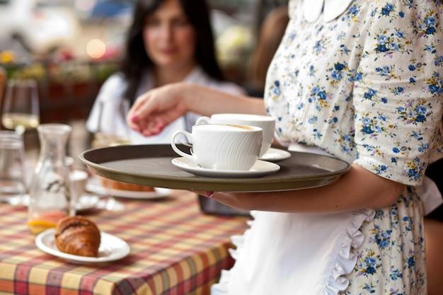 Kellnerin hält tablett mit tassen kaffee in der cafeteria