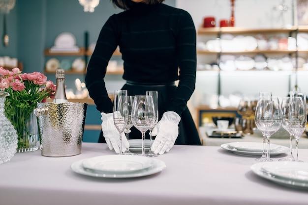 Kellnerin in handschuhen stellt das geschirr
