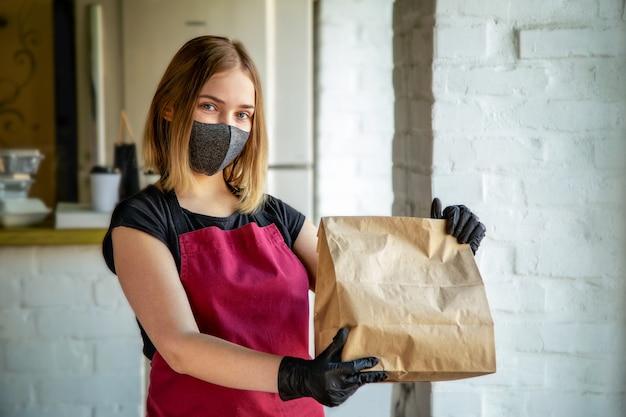 Kellnerin in medizinischer schutzmaske und handschuhen arbeitet mit bestellungen zum mitnehmen, die eine liefertasche halten