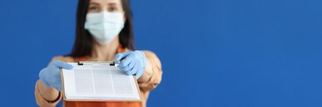Kellnerin in medizinischer schutzmaske und handschuhen, die zwischenablage mit dokumenten und stift für signa...