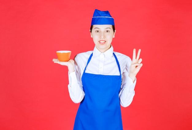 Kellnerin in uniform, die eine orangefarbene schüssel hält und victory-zeichen zeigt.