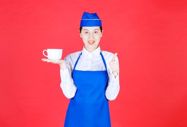 Kellnerin in uniform, die eine tasse hält und daumen auf der roten wand zeigt.