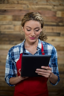 Kellnerin mit digitalem tablet gegen holzwand
