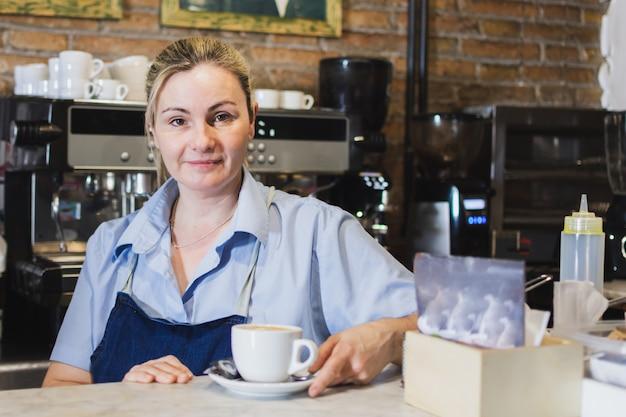Kellnerin mit einer tasse kaffee hinter der cafeteria-bar