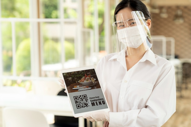 Kellnerin mit gesichtsschutz und gesichtsmaske zeigt das menü