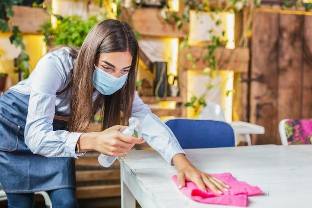 Kellnerin mit gesichtsschutzmaske beim desinfizieren von tischen im restaurant oder im café für den nächsten kunden. corona-virus und kleinunternehmen sind offen für arbeitskonzepte.