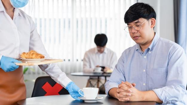 Kellnerin mit schützender gesichtsmaske und handschuhen zur verhinderung von ausbrüchen coronavirus