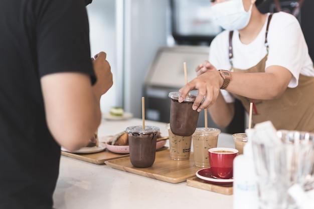 Kellnerin mit schutzmaske, die dem kunden im café eisgekühltes schokoladengetränk serviert