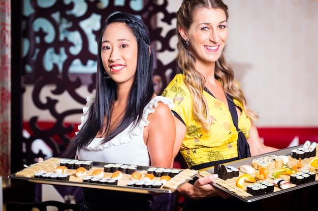 Kellnerin mit sushi im asiatischen restaurant