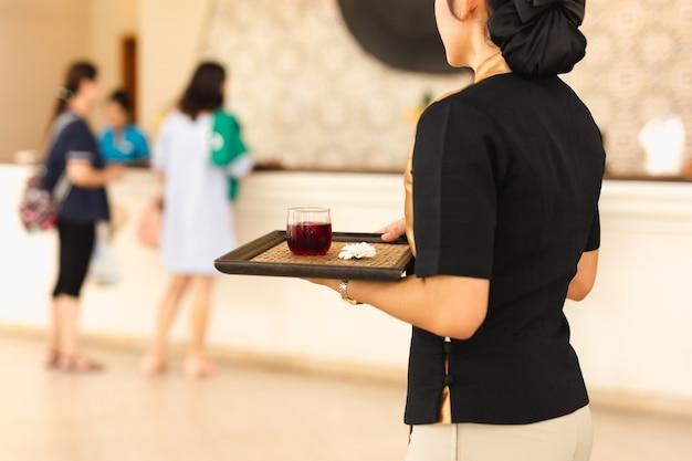 Kellnerin mit willkommensgetränk auf einem tablett bei hotle
