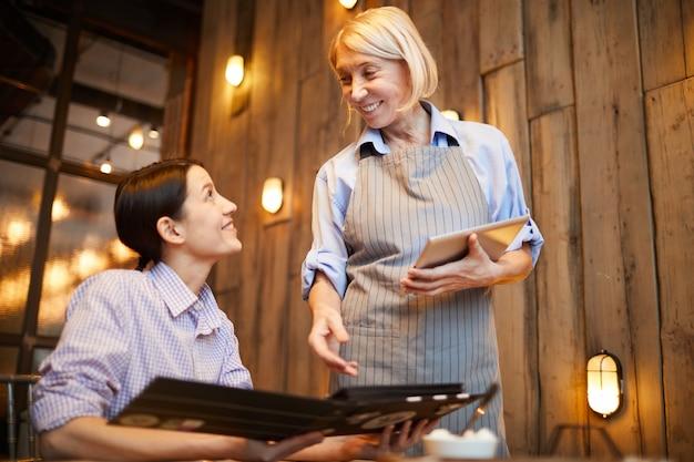 Kellnerin nimmt bestellung im restaurant auf