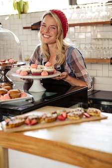 Kellnerin posiert mit kuchen