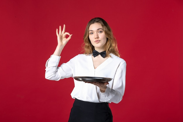 Kellnerin schmetterling am hals und hält tablett, die brillengeste auf rotem hintergrund macht