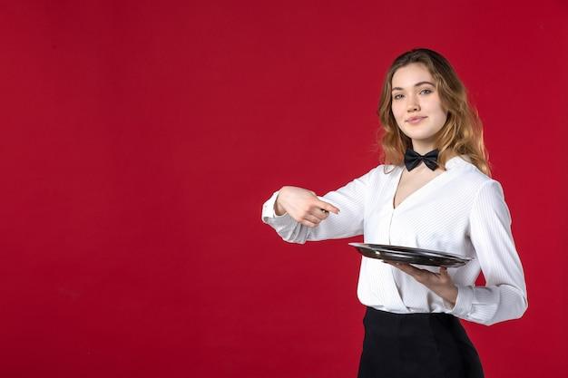 Kellnerin schmetterling am hals und zeigt tablett auf rotem hintergrund