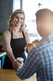 Kellnerin serviert dem kunden eine tasse kaffee und ein croissant