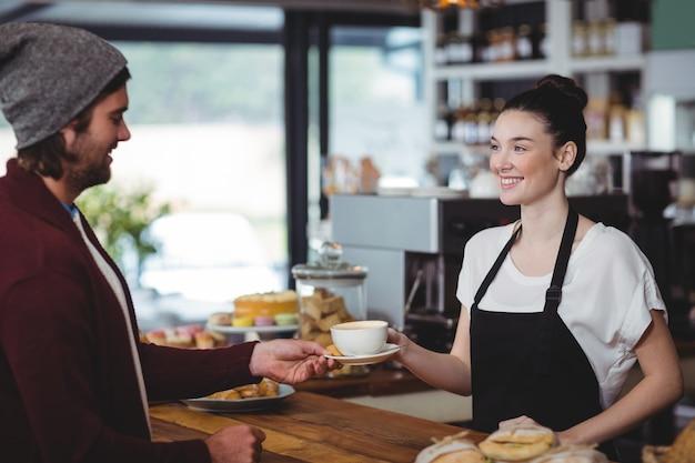 Kellnerin serviert dem kunden eine tasse kaffee