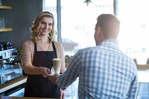 Kellnerin serviert dem kunden eine tasse kalten kaffee
