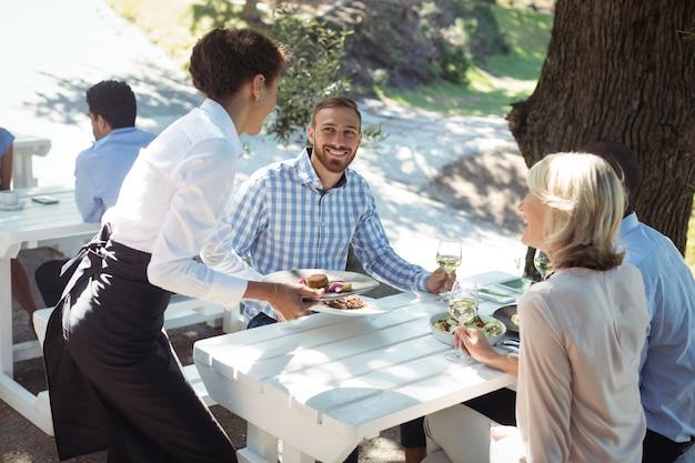Kellnerin serviert den kunden essen