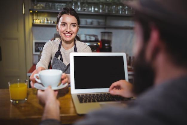 Kellnerin serviert eine tasse kaffee zu kunden