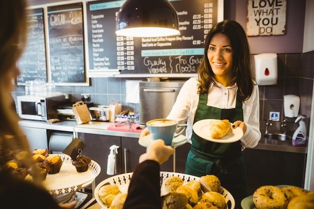 Kellnerin serviert eine tasse kaffee