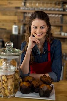 Kellnerin serviert eine tasse kuchen an der theke