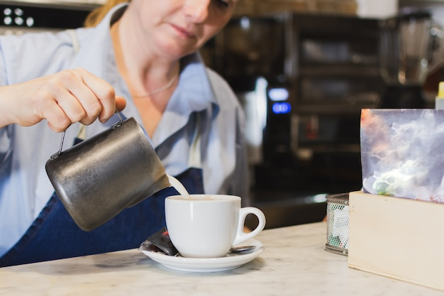 Kellnerin serviert milch in der kaffeetasse hinter der bar