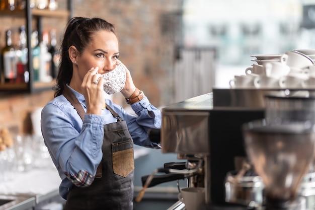 Kellnerin setzt in einem café eine gesichtsmaske auf, da die regierung maßnahmen ergriffen hat, um die ausbreitung des coronavirus zu begrenzen.