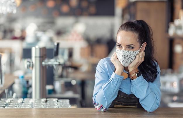 Kellnerin steht in einem kaffeehaus ohne zu tun, trägt schutzmaske und wartet auf kunden.