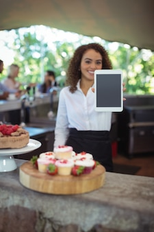 Kellnerin zeigt digitales tablet im straßencafé