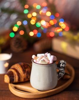 Keramikbecher mit kakao und marshmallows und einem gebackenen croissant auf einem braunen tisch hinter weihnachtslichtern