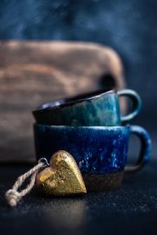 Keramikbecher und herzförmige dekoration für das abendessen zum valentinstag