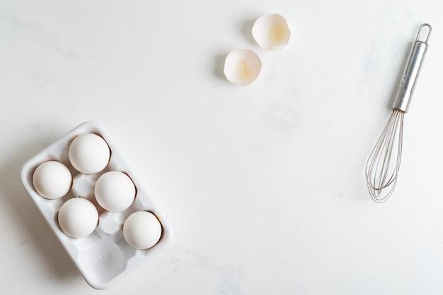 Keramikbox mit natürlichen bio-eiern und schneebesen auf einem steinernen küchentisch.
