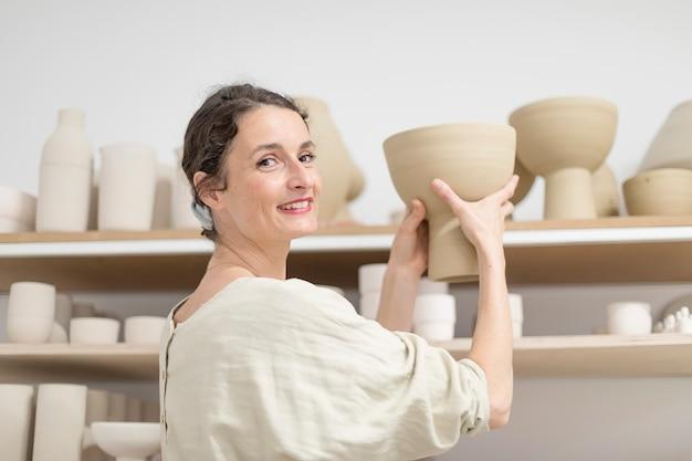 Keramikerfrau, die einen töpfer in ihrem studio hält