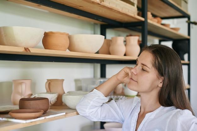 Keramikerin steht auf dem hintergrund eines regals mit handgefertigten tonutensilien