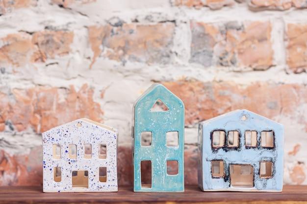 Keramikfiguren des hauses ohne dach gegen mauer.