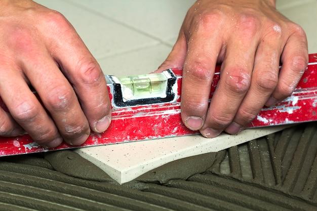 Keramikfliesen und werkzeuge für fliesenleger. arbeitskrafthand, die bodenfliesen installiert. hauptverbesserung, erneuerung - keramischer fliesebodenkleber, mörtel, niveau.