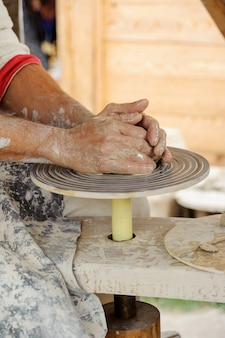 Keramikhände des meisters machen tonkrug auf der töpferscheibe