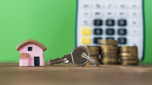 Keramikmodell eines rosa hauses mit den münzen und dem schlüssel