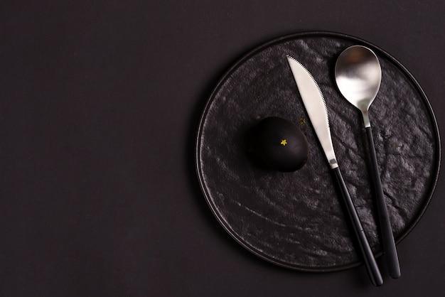 Keramikplatte, löffel und messer mit gemaltem schwarzem osterei auf dem schwarz.