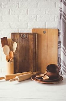 Keramikplatten, holz- oder bambusbesteck, schneidebretter und handtuch im kücheninnenraum.
