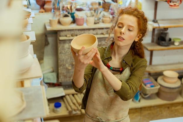 Keramiksammlung. konzentrierte junge dame in schutzschürze, die den fertigen topf von allen seiten betrachtet