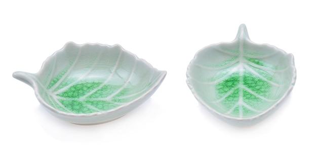 Keramikschale der grünen blattform lokalisiert auf weiß