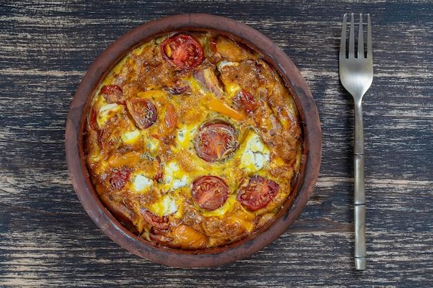 Keramikschale mit gemüsefrittata, einfaches vegetarisches essen. frittata mit tomaten, paprika, zwiebeln und feta-käse auf holztisch, nahaufnahme. italienisches eieromelett, ansicht von oben