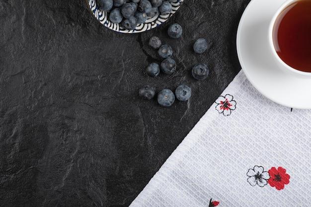 Keramikschale mit köstlichen frischen blaubeeren und einer tasse tee auf schwarzer oberfläche